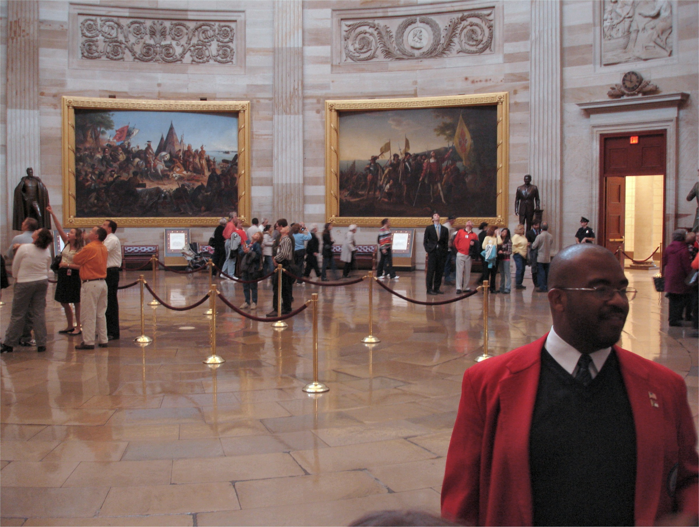 A tour guide in red blazer describing the rotunda's art and.